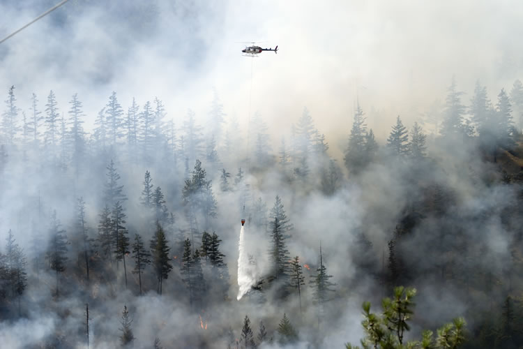Forest fire emitting large quantities of smoke with a helicopter dropping water on the fire.