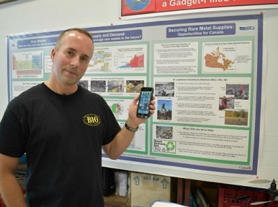 NRCan reseach scientist Michael Parsons stands in front of a poster board with a cell phone in his left hand