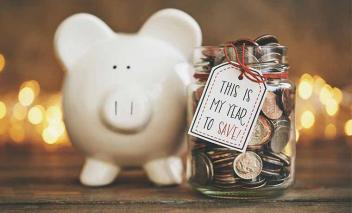 "Piggy bank beside a jar of coins that says ""This is my year to save""."