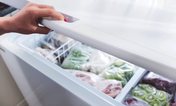 Person opens chest freezer.