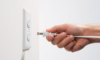 Man's Hand Inserting Electrical Power Cord Plug into Receptacle on wall outlet