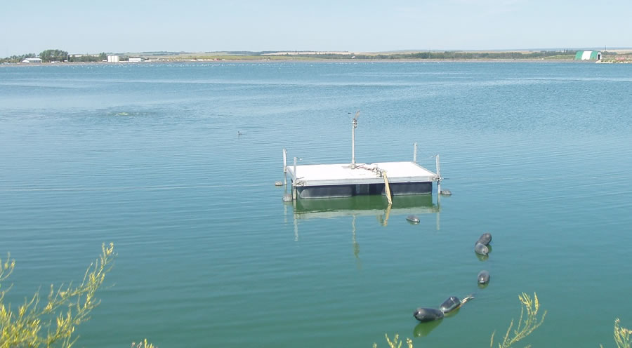 Sewage lagoon with floating pump platform in Clairmont, Alberta