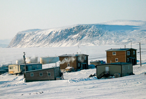 A winter photograph of several houses of Clyde River with mountainous snow covered terrain in the background