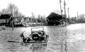Archival photograph of old submerged car on flooded street in London Ontario
