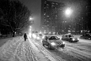 nighttime photograph showing vehicles and pedestrian on snow covered Quebec City street