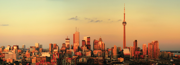 Photograph of the Toronto skyline illuminated by the setting sun