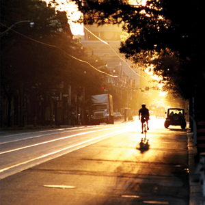 Photograph of a road cyclist with the rising sun at his back