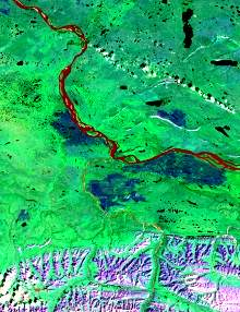 The image has a predominant green component with red tones in the water bodies due to sediment