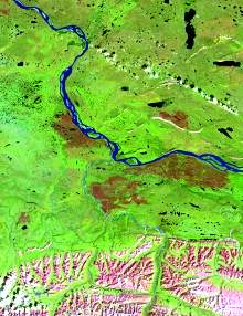The image has a predominant green component with some blue tones in the water bodies due to sediment