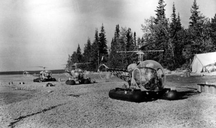 Three helicopters on the ground with a tent to the left side with trees in the background