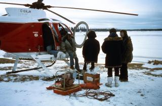 Airplane on the ground with technician and equipment with snow in the background