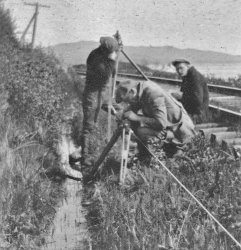 Technicians taking measurements with a precise traverse on the side of a railroad track in a ditch