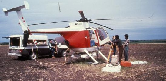 Airplane on the ground with technicians and equipment in a field.
