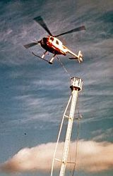 Helicopter erecting a tower with a sky background