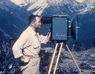 Technician looking through a tellurometer on a tripod with mountains in the background