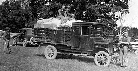 Motorized truck in a field with technicians standing around and on top of the truck with car in the background