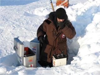 Technician kneeling taking gravity measurements on the snowy ground