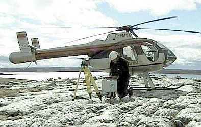 Technician kneeling on rock outcrop taking measurements with a CG-5 gravimeter with a helicopter in the background