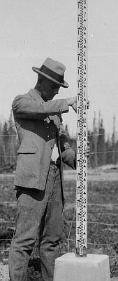 Technician taking a measurement with an Invar rod