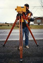 Technician operating a level on a tripod on the shoulder of a road