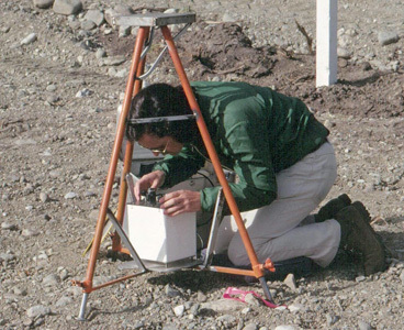 Technician kneeling on the rocky ground taking measurements with a Lacoste-Romberg gravimeter
