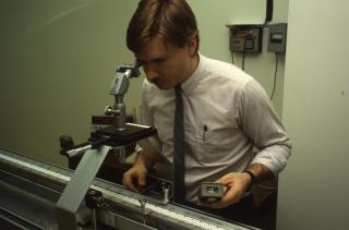 Technician taking a measurement indoors using a rod calibration bench
