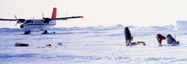 Technicians working with equipment in the snow with a grounded plane in the background