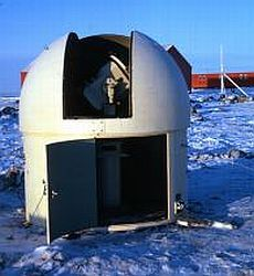 Surveying equipment in a dome on snow with a building in the background