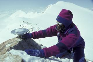 Technician on snowy mountaintop in winter attire holding a GPS antenna with a mountainous backdrop