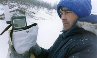 Technician holding a handheld GPS outside in the wintertime