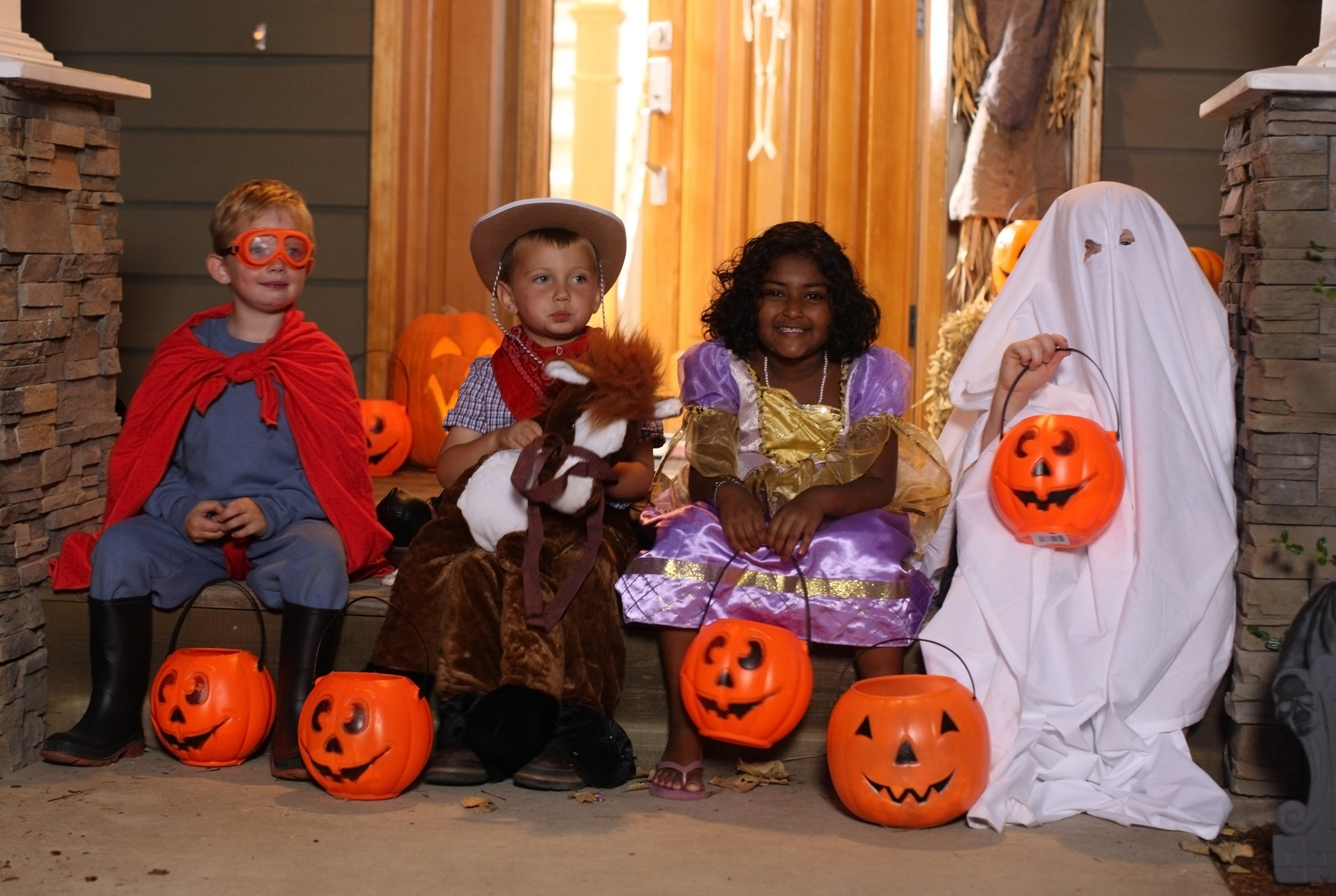 Children sitting on front porch in Halloween costumes