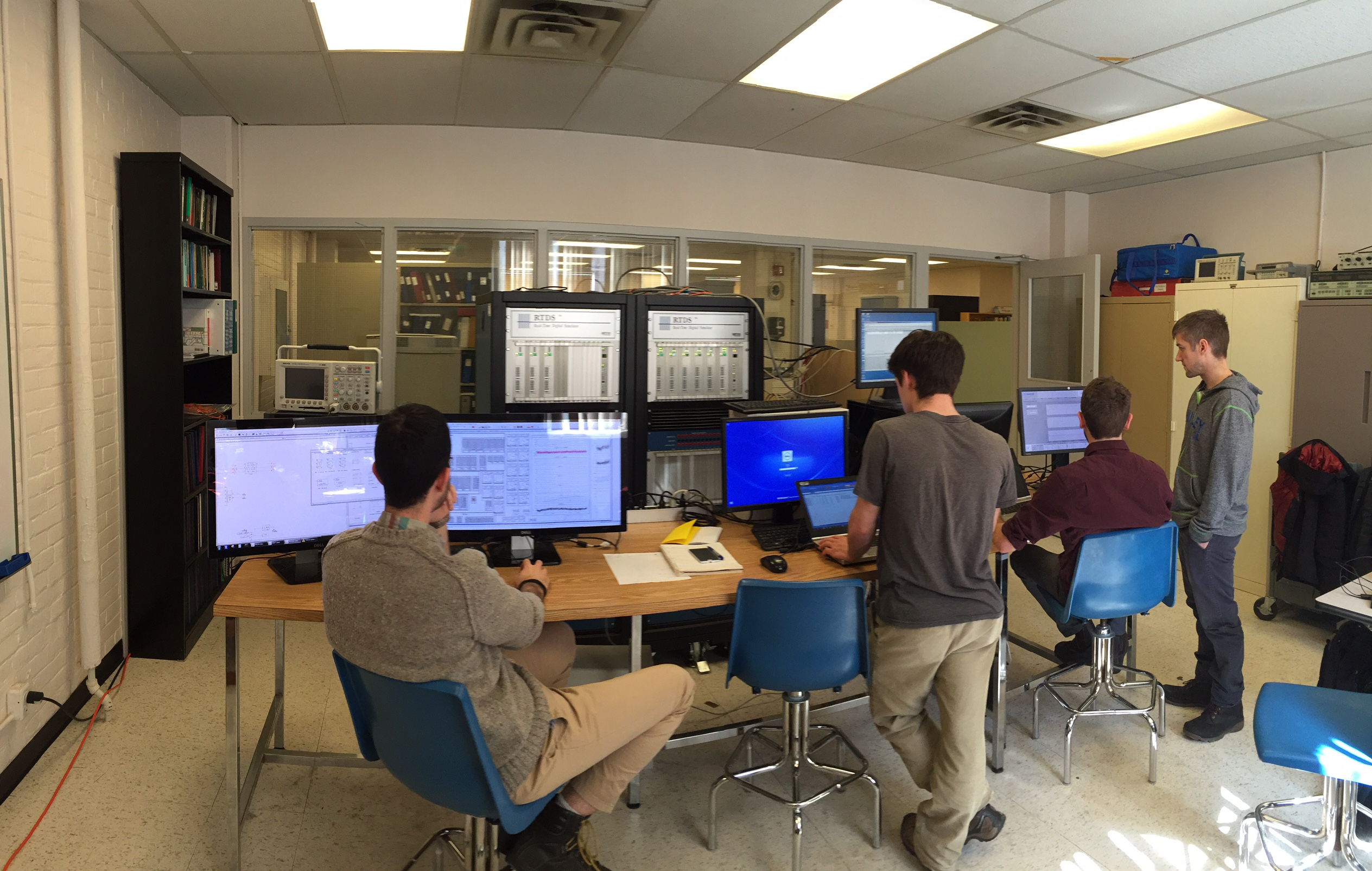 Test facility environment with 4 engineers from Hatch working at computer terminals connected to real time simulator and microgrid controls hardware