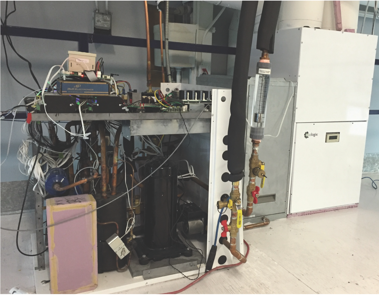 The photo shows the interior of the Ecologix prototype integrated heat pump module, connected to various instruments for laboratory testing, with its air handler in the background