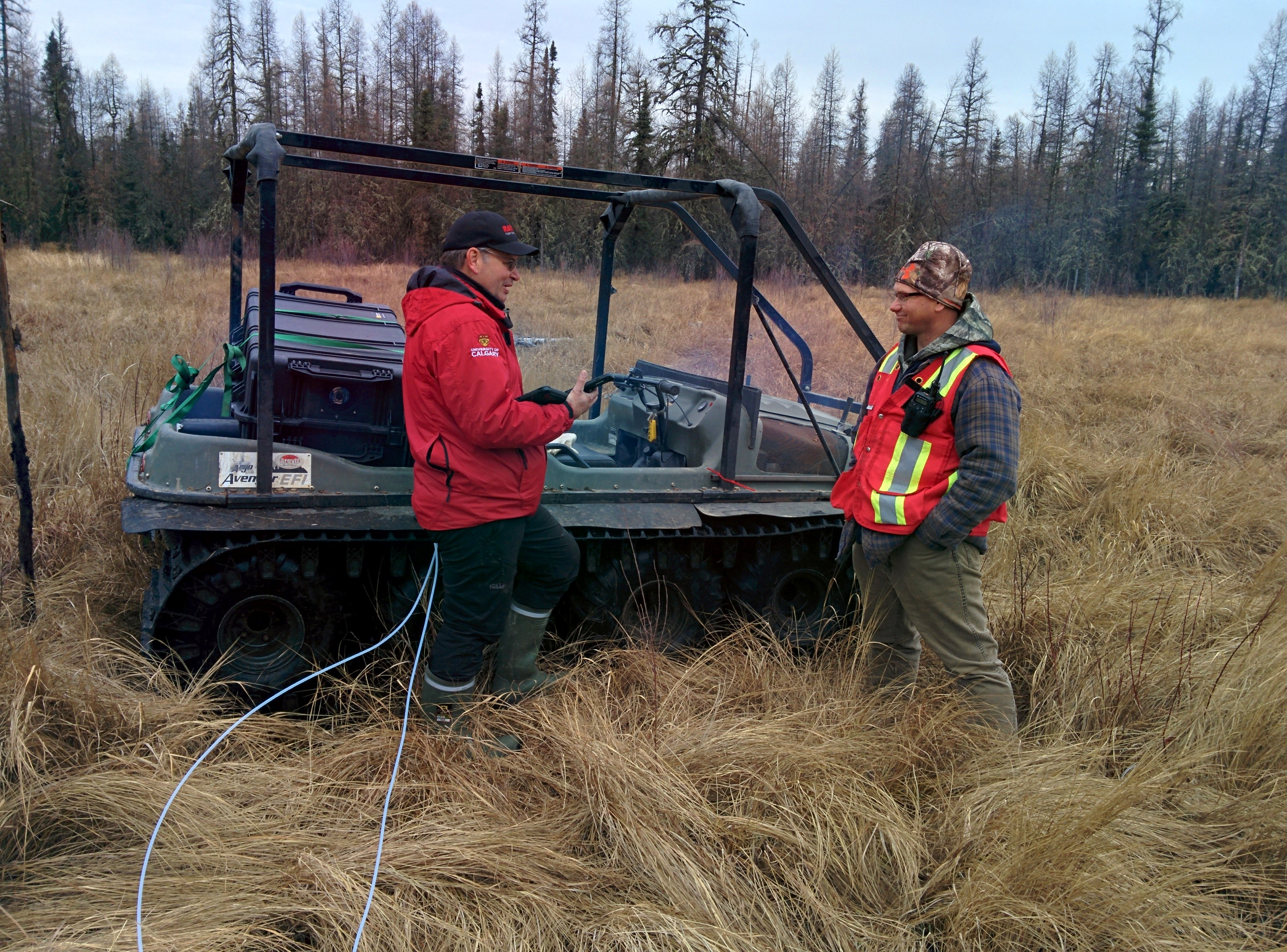 Two researchers stand beside the Argo, loaded with atmospheric leak detection technology, in a grassy, wetland in Christina Lake, Alberta.