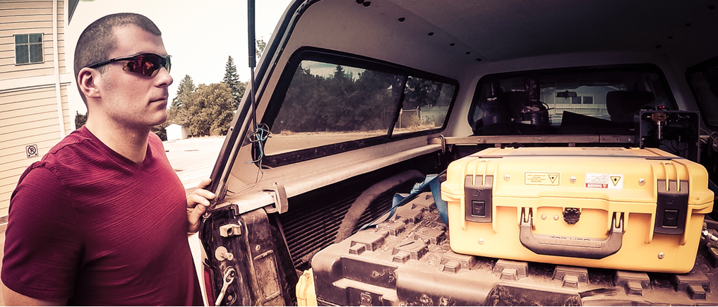 Flux Lab researcher, James Williams, with research truck ready for another day of fugitive emissions mapping. The research truck pictured is Toyota Tacoma with a cap that stores the detection equipment while data is collected.