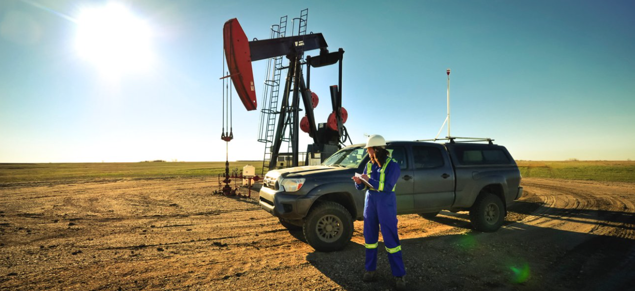 Flux Lab Researcher, Jennifer Baillie, with research truck parked in front of oil field pump jack located in Weyburn, SK. Jennifer takes notes on a clipboard outside of the research truck.
