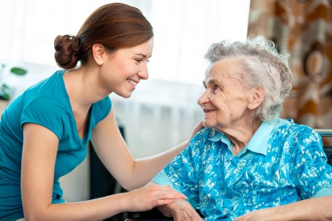 Image of an elderly woman and a caretaker