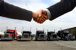 Shaking of hands in front of parked trucks