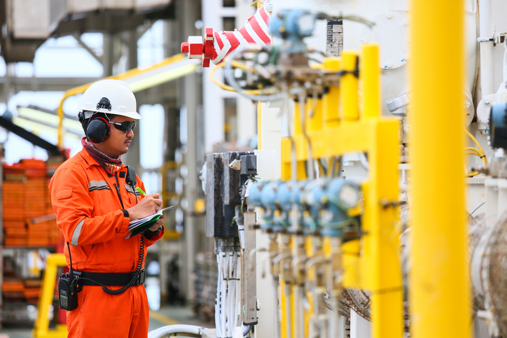 Gas plant operator recording operation of gas process