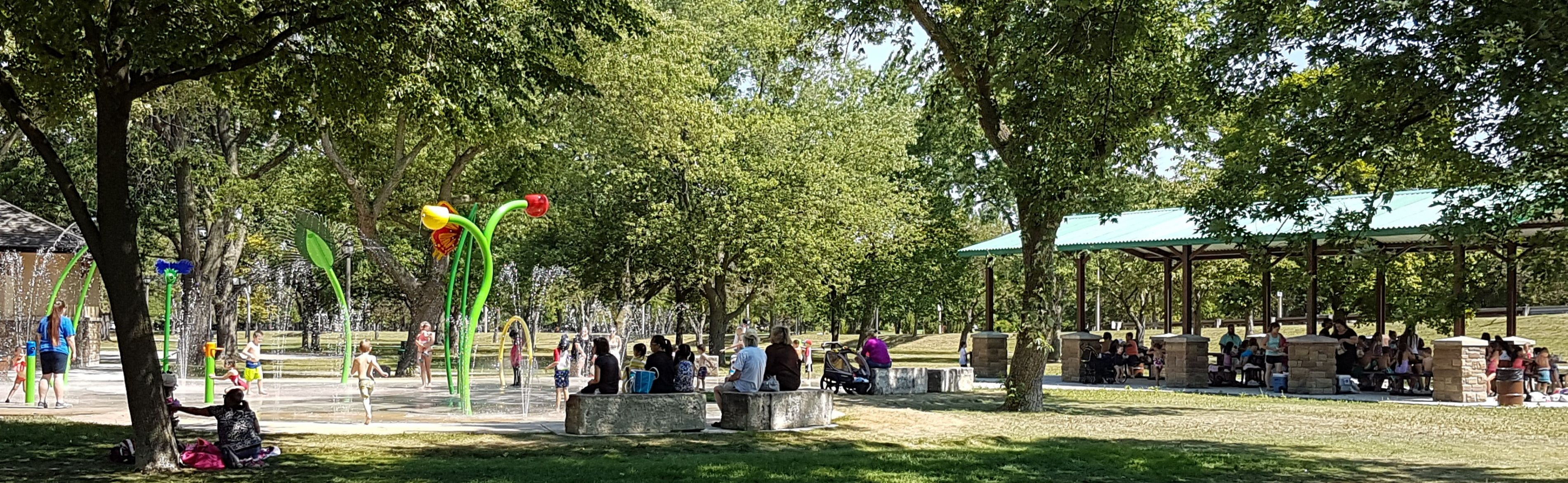 Photograph of a park with trees, shade structure  and splash pad in Windsor. Photo credit: City of Windsor