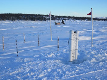 Photo of a SmartICE stationary buoy in the ice (right foreground) next to a manually operated snow-and-ice monitoring station (wooden stakes inserted in the snow) near Nain, Nunatsiavut. Photo credit: Trevor Bell