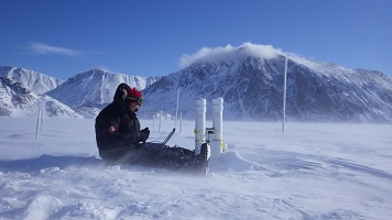Photo showing geographer Trevor Bell checking a SmartICE sensor in Eclipse Sound, Nunavut. Photo credit: Trevor Bell