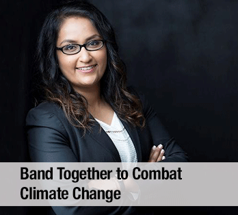 A woman wearing a suit and glasses in front of a dark background - Band together to combat climate change