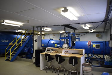 A blue large metallic tube that is the Accuair wind tunnel inside an NRCan laboratory.
