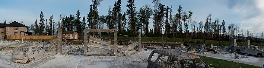 A photo of a burned out neighbourhood in Fort McMurray showing rubble from houses and burnt cars in the foreground with trees in the background.