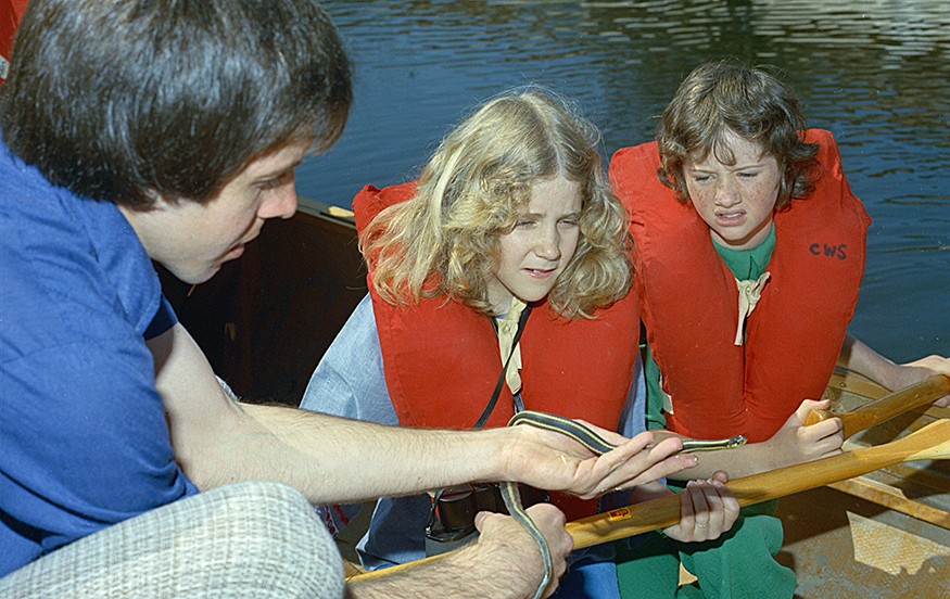 A colour photo from the 1970s depicting a forest educator showing a small snake to a boy and a girl wearing life jackets in a canoe.