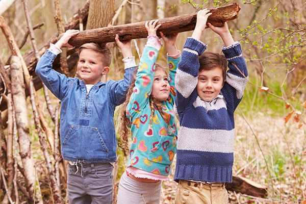 Children carrying a branch together.