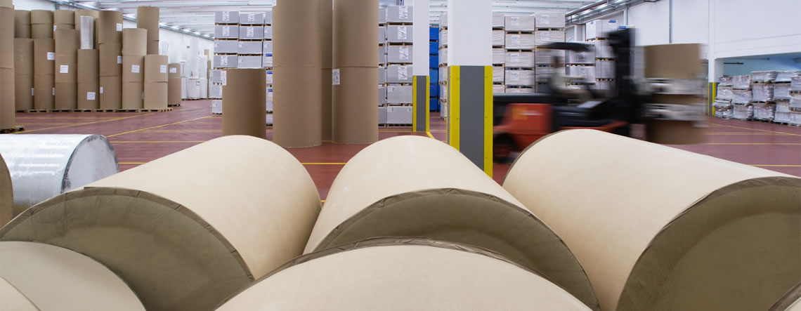 Large spools of brown paper in a warehouse.