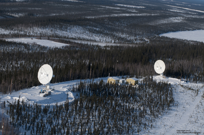 A view of the Inuvik Satellite Station Facility with two dish antennas and 2 buildings amongst the pine trees and snow. (Copyright 2012 Terry Halifax Photography)
