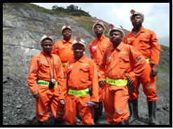 Six men with orange mining gear and hard hats
